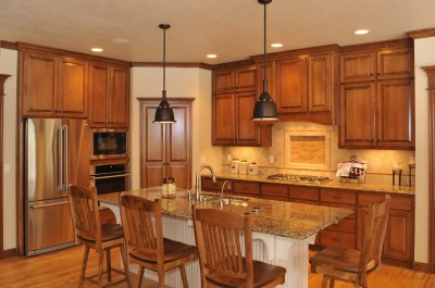 Two toned cabinetry, paneled wood hood, stacked upper cabinets, island with bead board back and sides